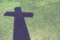Ombra dell'incrocio cristiano sul pavimento dell'erba verde con il filtro d'annata Immagini Stock Libere da Diritti
