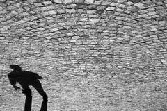 Ombra di un uomo sulla vecchia strada cobbled Fotografie Stock