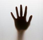 Ombra di una mano confusa dietro il vetro glassato immagini stock libere da diritti