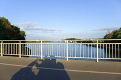 Ombra di una motocicletta su un ponte fotografia stock