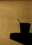 Ombra di una tazza di carta del caffè su una tavola Immagine Stock Libera da Diritti