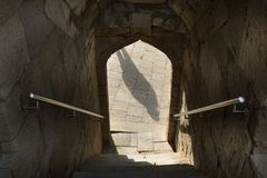 Ombra nella entrata dell'arco, inferriata, scale giù l'entrata attraverso l'arco fotografia stock libera da diritti