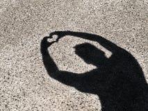 Ombra Silhoutte che si tiene per mano nella forma del cuore fotografia stock libera da diritti