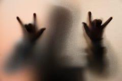 Ombragez la tache floue de l'homme d'horreur dans la veste avec le capot Le doigt font comme sym Photo libre de droits