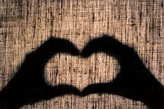 Ombragez les mains et les doigts sous forme de coeur sur la toile de toile Photo libre de droits