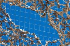 Ombre bleue blanche légère déchirée militaire de filet de camouflage de ciel photographie stock libre de droits