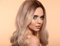 Ombre blond wavy hairstyle. Beauty fashion blonde woman portrait. Beautiful girl model with makeup, long healthy hair style posing stock image