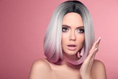 Ombre bob short hairstyle. Beautiful hair coloring woman with wow face holding hand near her cheek isolated on pink studio royalty free stock photos