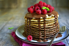 Ombre chocolate pancakes with fresh raspberry and chocolate sauc. E on a vintage plate on rustic wooden background Stock Image