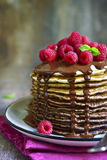 Ombre chocolate pancakes with fresh raspberry and chocolate sauc. E on a vintage plate on rustic wooden background Stock Photography