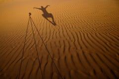 Ombre d'un photographe faisant de la lévitation à côté de sa fonte de trépied Image libre de droits