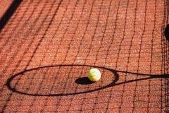 Ombre d'une raquette et d'une boule de tennis sur la cour Photographie stock