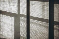 Ombre dai ciechi e dalla finestra sulla parete fotografia stock libera da diritti