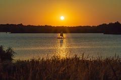 Ombre de bateau à voile avec le contour clair du soleil au coucher du soleil avec le bel horizon au-dessus du lac Zorinsky Omaha  image stock