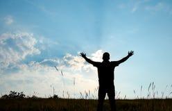 Ombre de culte de l'homme avec des mains augmentées au ciel dans l'esprit de nature Image libre de droits