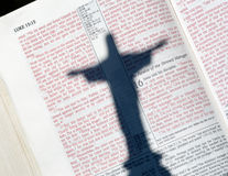 Ombre de Jésus sur la bible à marquer d'une pierre blanche avec Luc Photos stock