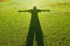 Ombre de la personne sous forme de croix sur une herbe Photos libres de droits