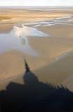 Ombre de Mont Saint Michel Abbey sur les sables de tremblement Image stock