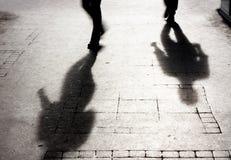 Ombre de pour deux personnes sur le trottoir patterened Photos stock