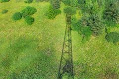 Ombre de tour de télécommunication avec les antennes par radio et les antennes paraboliques sur le champ vert avec l'herbe, buiss image stock