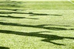 Ombre des hommes courant sur le champ vert Photographie stock libre de droits