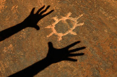 Ombre des mains adorant la pétroglyphe de Sun Photos stock