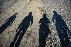 Ombre des personnes marchant la route pendant le coucher du soleil images stock
