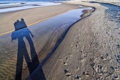 Ombre des personnes marchant sur une plage par la mer baltique Images libres de droits