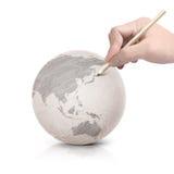 Ombre dessinant la carte de l'Asie sur la boule de papier Photos stock