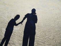 Ombre du père et de la fille sur la plage sur la plage, ombre des personnes photographie stock libre de droits