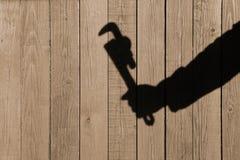 Ombre humaine de main avec la clé réglable sur le fond en bois Photo stock