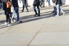 Ombre lunghe dei camminatori che camminano sulla pavimentazione luminosa della lastra di cemento armato fotografia stock