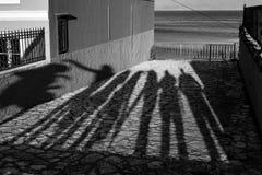 Ombre lunghe di pomeriggio di sette persone e del mare fotografie stock libere da diritti