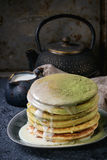 Ombre matcha pancakes. Stack of homemade american ombre green tea matcha pancakes with condensed milk sauce and matcha powder served on gray plate with jug of Stock Images