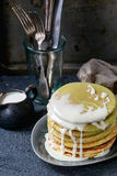 Ombre matcha pancakes. Stack of homemade american ombre green tea matcha pancakes with condensed milk sauce served on gray plate with jug of cream and cutlery Royalty Free Stock Images