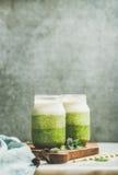 Ombre mergulhou batidos verdes com a hortelã fresca nos frascos de vidro Fotos de Stock