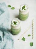 Ombre mergulhou batidos verdes com a hortelã nos frascos de vidro Foto de Stock Royalty Free