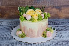 Ombre wedding cake decorated with roses and some greenery. An ombre wedding cake decorated with roses and some greenery Stock Images