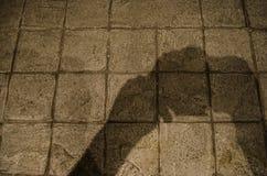 Ombreggi le mani di un uomo che tiene una macchina fotografica sul pavimento di calcestruzzo di una via urbana fotografia stock