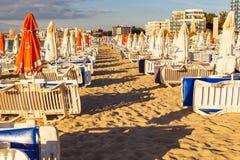 Ombrelli di spiaggia e chaise-lounge del sole su una spiaggia Fotografia Stock