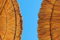 Ombrelli di spiaggia fatti di paglia al fondo del cielo blu Immagini Stock Libere da Diritti