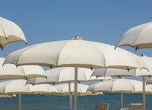 Ombrelli di spiaggia, gazebos e letti del sole alle spiagge sabbiose italiane Regione adriatica di Emilia Romagna della costa Immagini Stock