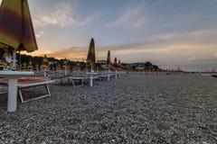 Ombrelli di spiaggia vicino alla città di Numana al tramonto, Conero NP, mA Fotografie Stock Libere da Diritti