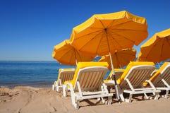 Ombrelli gialli luminosi su una spiaggia di sabbia Immagine Stock