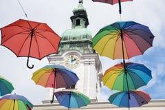 Ombrelli multicolori che appendono davanti alla chiesa immagini stock
