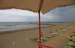 Ombrelli sulla spiaggia senza gente dal watchin del bagnino Fotografia Stock