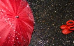 Ombrello bagnato e stivali di gomma del ` s dei bambini su asfalto bagnato fotografia stock libera da diritti
