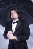 Ombrello della holding dell'uomo nella pioggia e nel sospirare Fotografia Stock Libera da Diritti