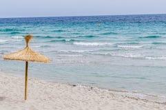 Ombrello della paglia sulla spiaggia di sabbia Immagine Stock