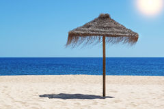 Ombrello della paglia sulla spiaggia vicino al mare blu. Immagine Stock